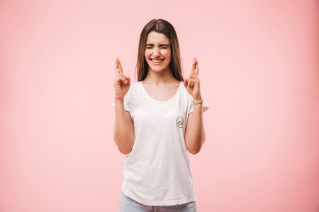 Portrait of an excited young woman holding fingers crossed for good luck isolated over pink background Banco de Imagens - 102275588