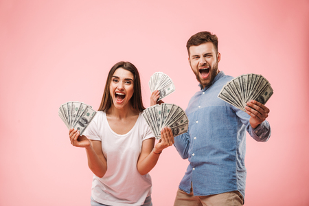 Portrait of an excited young couple holding bunch of money banknotes and celebrating success isolated over pink background