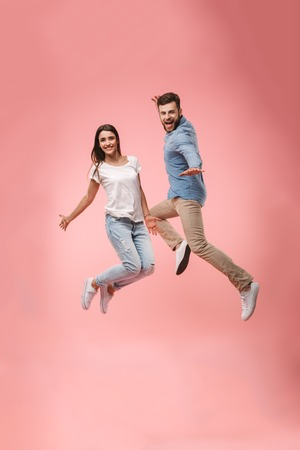 Full length portrait of a cheerful young couple holding hands while jumping isolated over pink background Archivio Fotografico