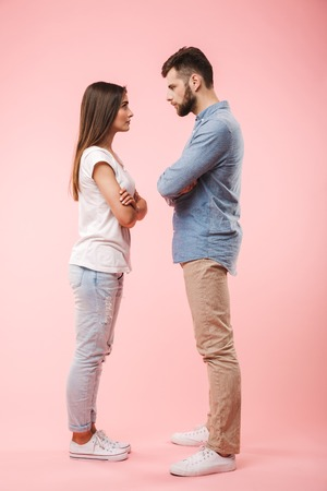 Full length portrait of an angry young couple standing with arms folded and looking at each other isolated over pink background Foto de archivo