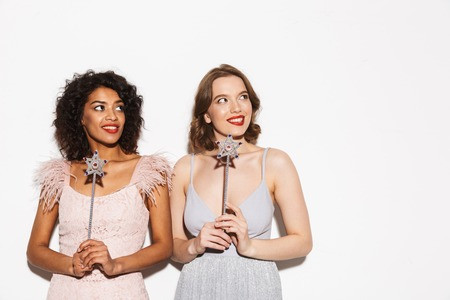 Portrait of two pretty well dressed women having fun with magical wands isolated over white background