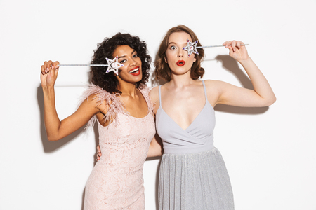 Portrait of two happy well dressed women having fun with magical wands isolated over white background