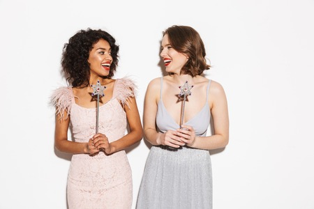 Portrait of two happy well dressed women looking at each other with magical wands isolated over white background