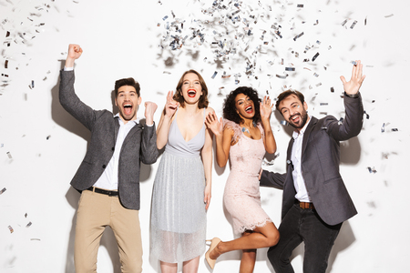 Group of happy well dressed multiracial people dancing together under confetti rain isolated over white background Stok Fotoğraf