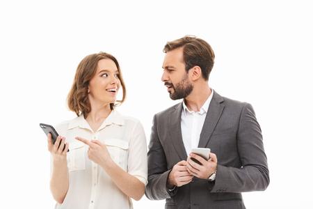Retrato de una pareja de negocios sonriente sosteniendo teléfonos móviles y hablando aislado sobre fondo blanco.