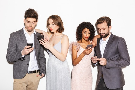 Group of bored well dressed multiracial people using mobile phones isolated over white background