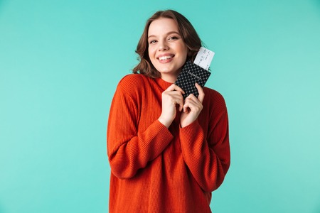 Portrait of a smiling young woman dressed in sweater holding passport with flying tickets isolated over blue background
