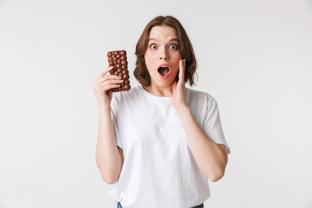Portrait of a shocked young woman holding chocolate bar isolated over white background Stock Photo - 102276197