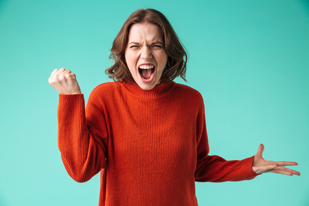 Portrait of an angry young woman dressed in sweater screaming isolated over blue background Stock Photo