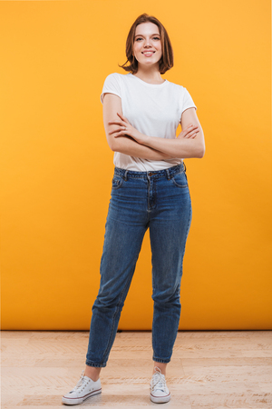 Image of happy young woman standing isolated over yellow background looking camera. Stock Photo