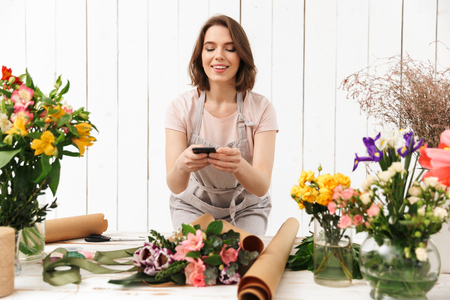 Beautiful florist woman in apron working in flower studio and taking photo with mobile phone of bouquet on table