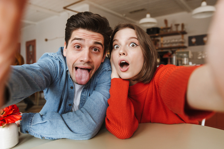 Caucasian couple woman and man having fun together and playing around at camera while taking selfie in cafe