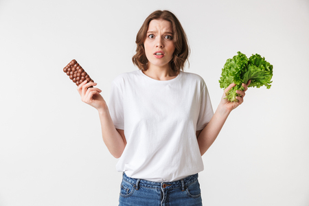 Portrait of a puzzled young woman holding chocolate bar and lettuce isolated over white background Stock Photo