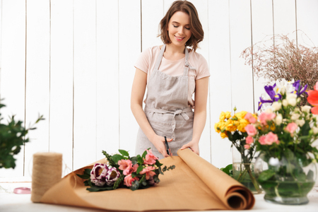 Photo of happy florist woman standing near table working with flowers in workshop. Stok Fotoğraf