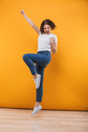 Photo of emotional young woman jumping isolated over yellow background make winner gesture.