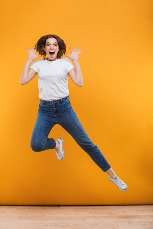 Photo of emotional young woman jumping isolated over yellow background. Looking camera.