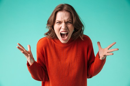 Portrait of a furious young woman dressed in sweater screaming isolated over blue background 스톡 콘텐츠