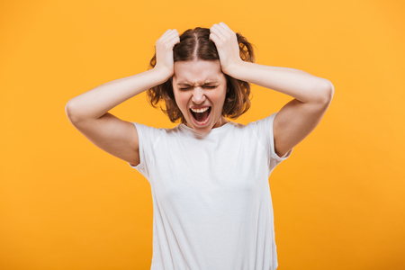 Image of agressive screaming young lady standing isolated over yellow background. 스톡 콘텐츠
