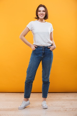 Image of happy young woman standing isolated over yellow background looking camera. Banque d'images - 102276228