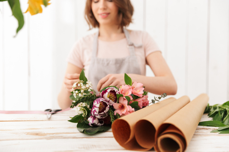 Blurry photo of young florist woman collecting bouquet of different flowers on table in workshop Stockfoto