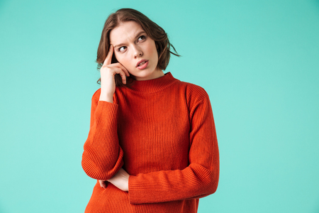 Portrait of a thoughtful young woman dressed in sweater looking away at copy space isolated over blue background