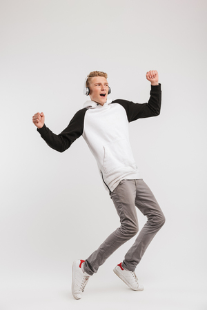 Full length portrait of teenage boy 16-18 years old wearing hoodie and wireless headphones having fun and dancing isolated over white background