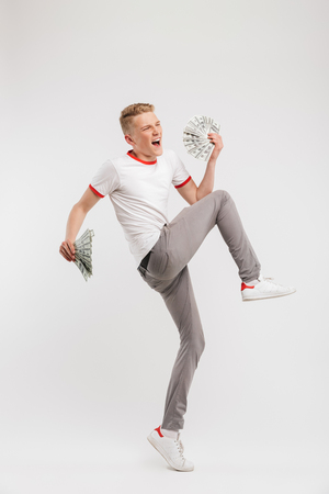 Full length portrait of successful young man wearing casual clothing screaming and jumping with two fans of cash money isolated over white background