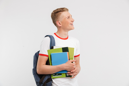 Image of thin teenage man university or college student wearing backpack looking aside at copyspace while holding textbooks isolated over white background Imagens