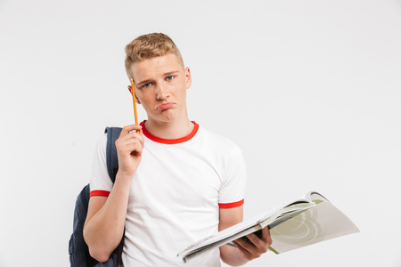 Image of young frustrated male student wearing backpack thinking while studying with textbooks and pen in hands isolated over white background