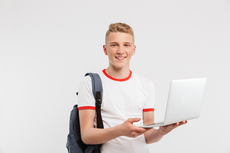 Image of teen man 16-18 years old wearing basic clothing and backpack holding open laptop with beautiful smile isolated over white background Stock Photo