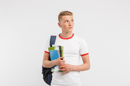 Image of young guy university or college student wearing backpack looking aside at copyspace while holding textbooks isolated over white background