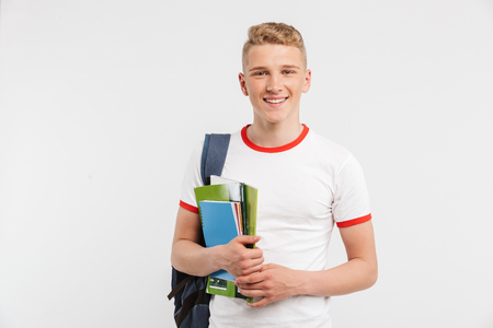 Image of european student boy wearing backpack smiling and looking at you with textbooks in hands isolated over white background