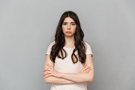 Image of displeased sad young lady standing isolated over grey background wall.