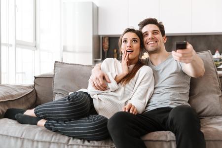 Porträt eines glücklichen jungen Paares, das auf einer Couch zu Hause beim Fernsehen entspannt