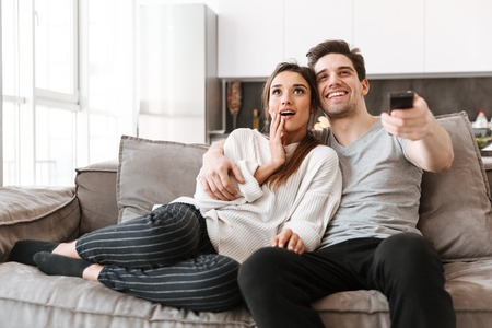 Retrato de una joven pareja feliz relajándose en un sofá en casa mientras ve la televisión