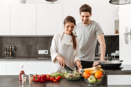 Portrait of a cheerful young couple cooking together at the kitchen