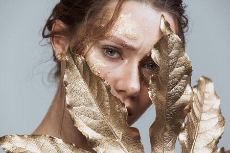 Beauty image of amazing brunette woman with soft healthy skin and golden makeup isolated over grey background looking camera holding golden leaf.