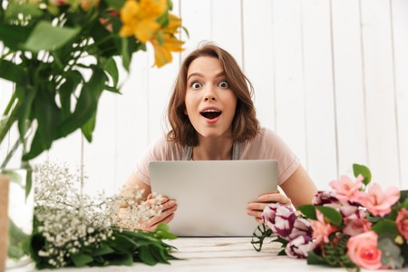 Young shocked florist lady standing with flowers in workshop using laptop computer. Looking camera.