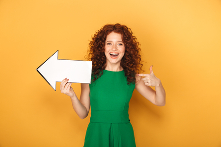 Portrait of a cheerful redhead woman in dress pointing away with an arrow isolated over yellow background