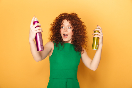Portrait of a happy curly redhead woman holding two hair sprays isolated over yellow background
