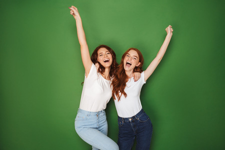 Portrait of two positive redhead women 20s smiling at camera with hands in air isolated over green background