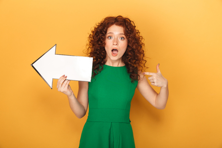 Portrait of an amazed redhead woman in dress pointing away with an arrow isolated over yellow background