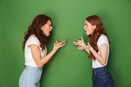 Two outraged girls 20s with ginger hair standing face to face crossed and shouting at each other isolated over green background