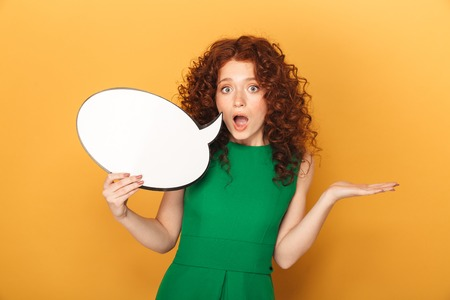 Portrait of a shocked redhead woman in dress holding empty speech bubble isolated over yellow background Archivio Fotografico