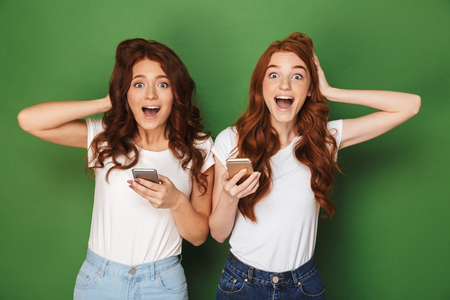 Portrait of two joyful women with ginger hair looking at camera and holding mobile phones isolated over green background