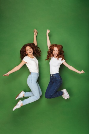 Full length portrait of two cheerful young redhead girls jumping together with arms raised isolated over green background