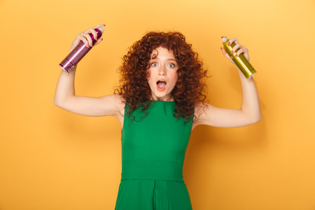 Portrait of a cheerful curly redhead woman holding two hair sprays isolated over yellow background