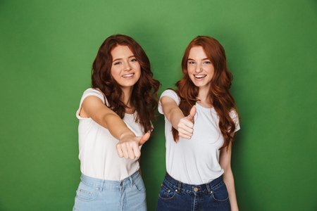 Portrait of two young redhead women 20s in casual wear smiling at camera and showing thumbs up isolated over green background