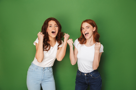 Portrait of two young redhead women 20s in casual wear rejoicing and clenching fists isolated over green background