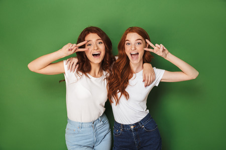 Portrait of two redhead teenage women 20s smiling and showing victory signs at face isolated over green background